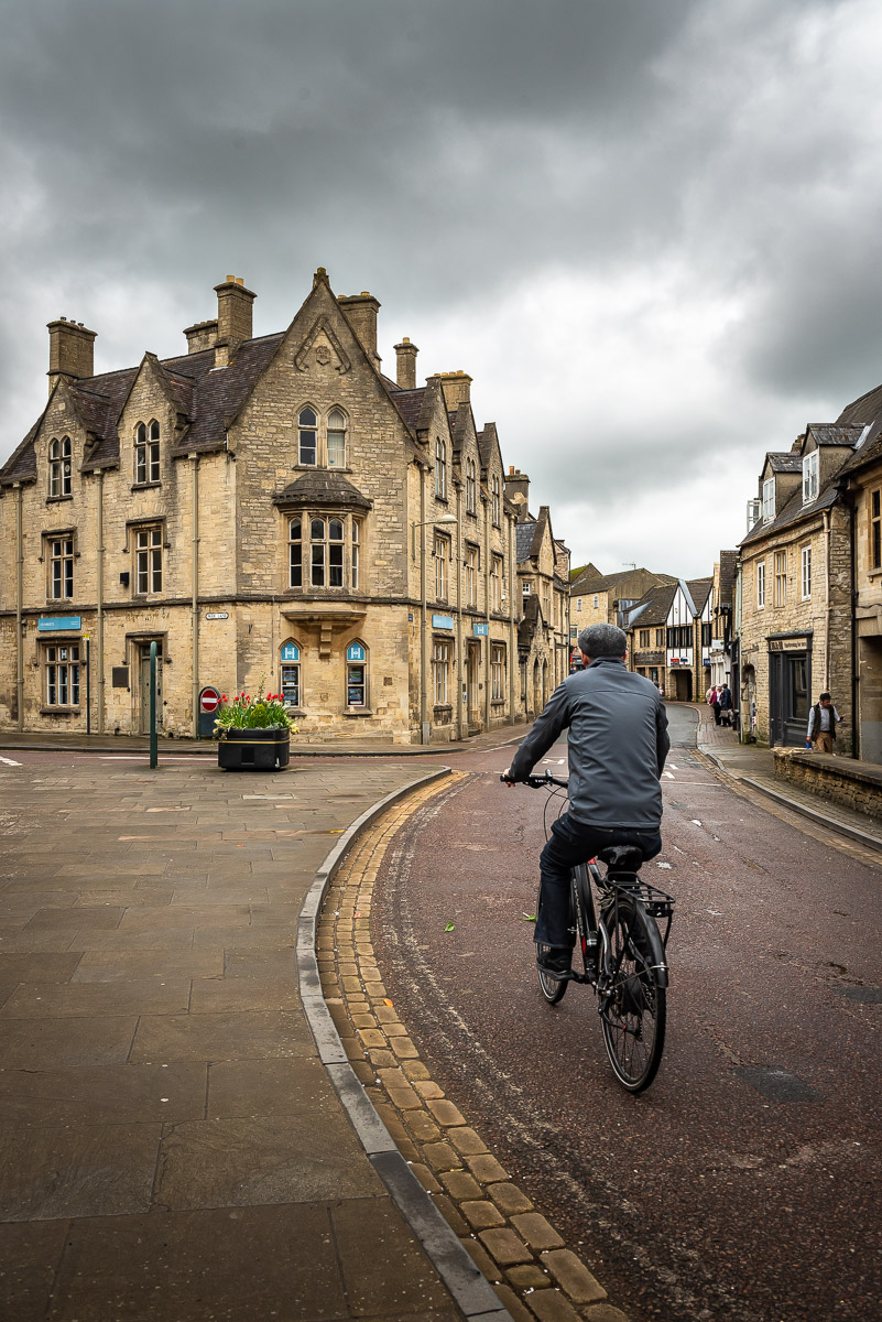 Man on a bike riding in a village in the Cotswolds in the English countryside