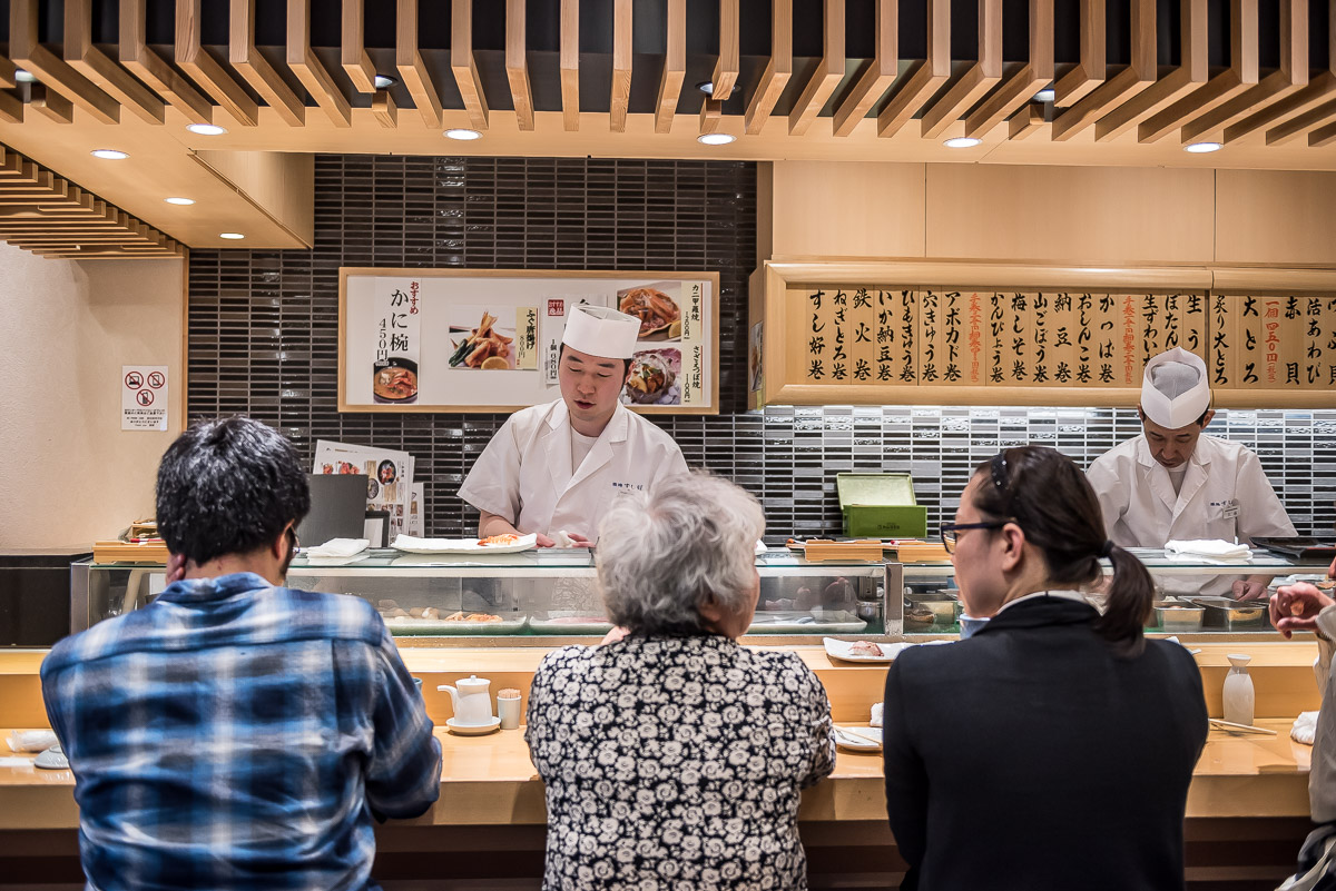 Japanese sushi restaurant with people dining at the counter and chefs