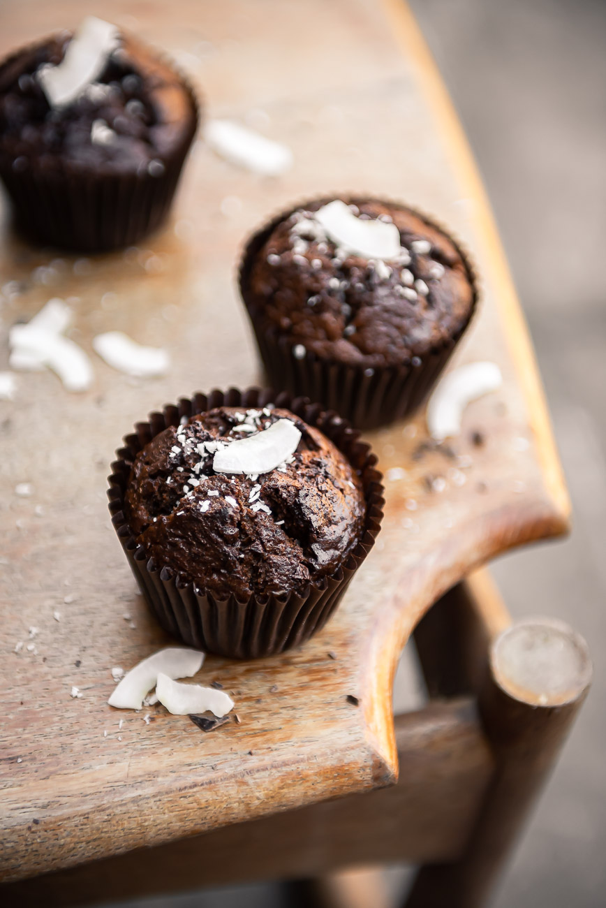 Three chocolate muffins on a light wooden table