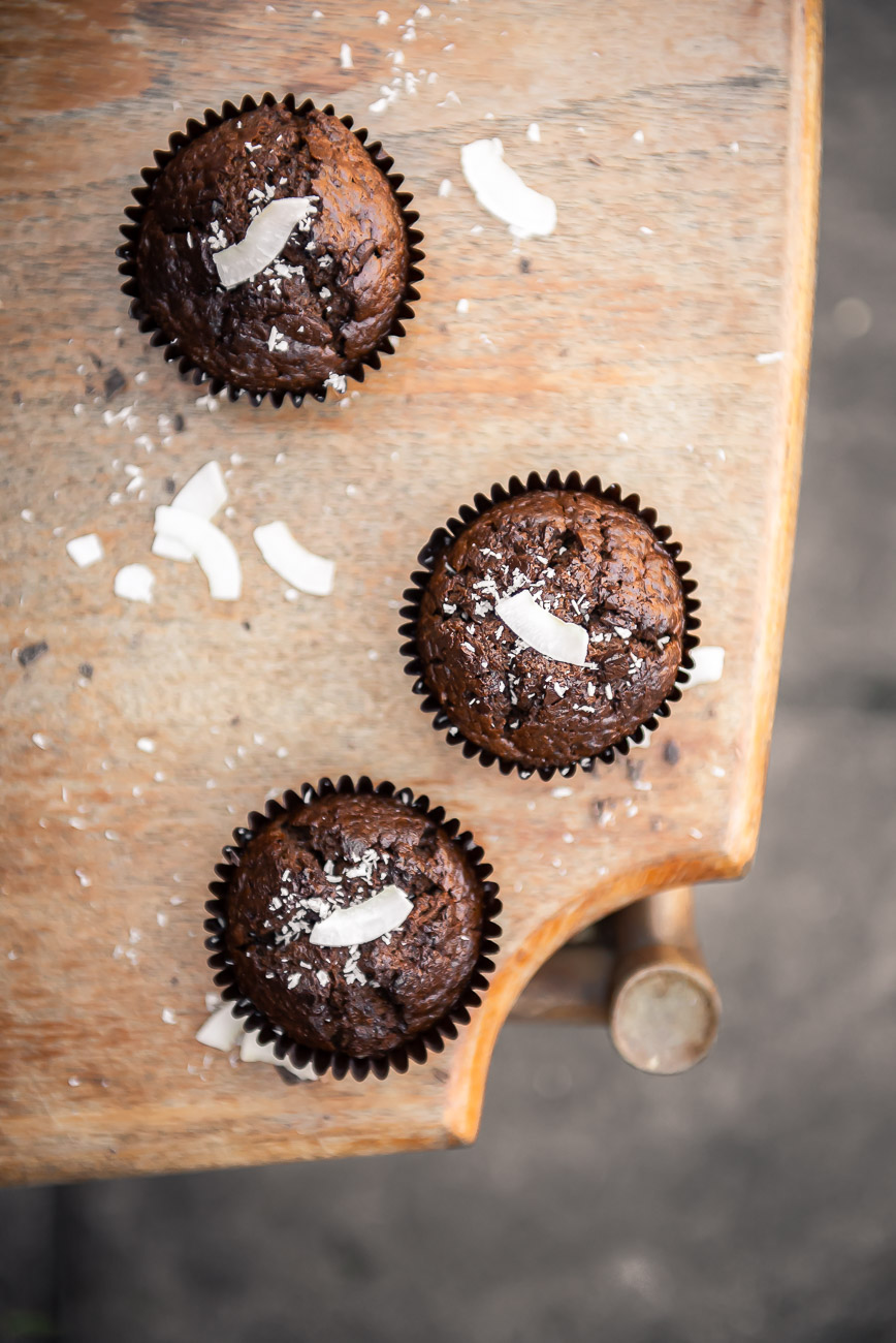 Three chocolate muffins on a light wooden table, top down view