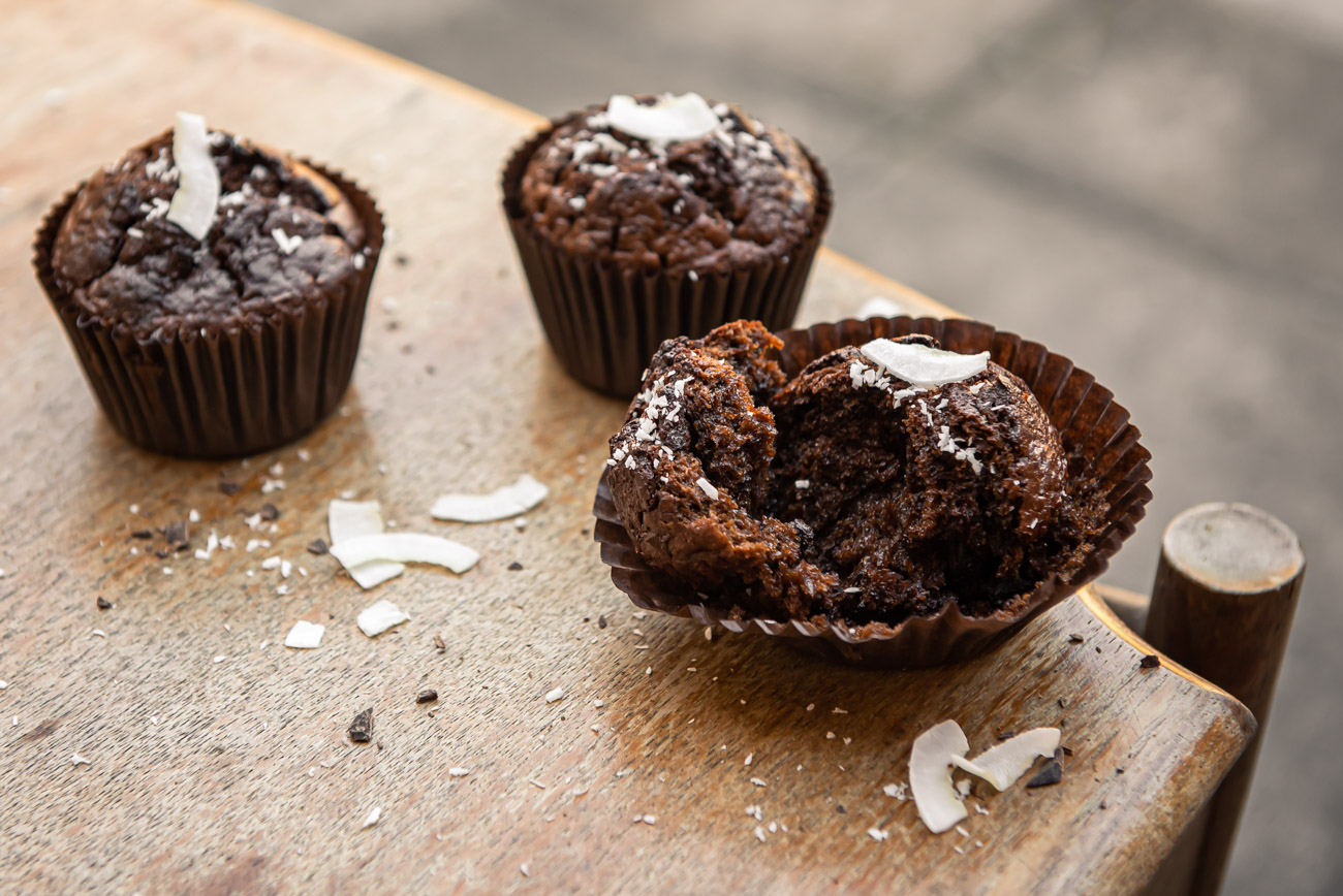 Three chocolate muffins on a light wooden table, one open
