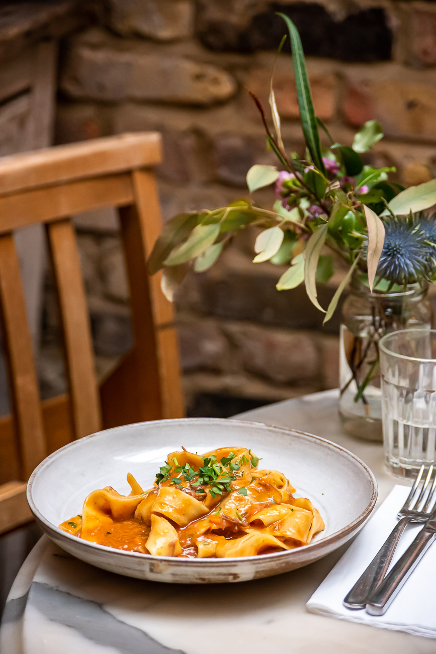 Plate of pasta on a marble table in a rustic restaurant set up