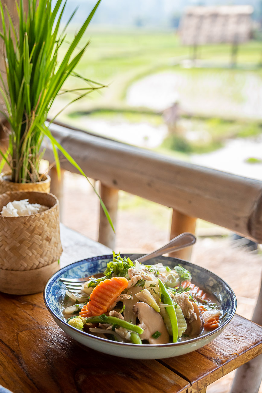 Stir fried chicken and vegetables on a balcony overlooking the rice paddies