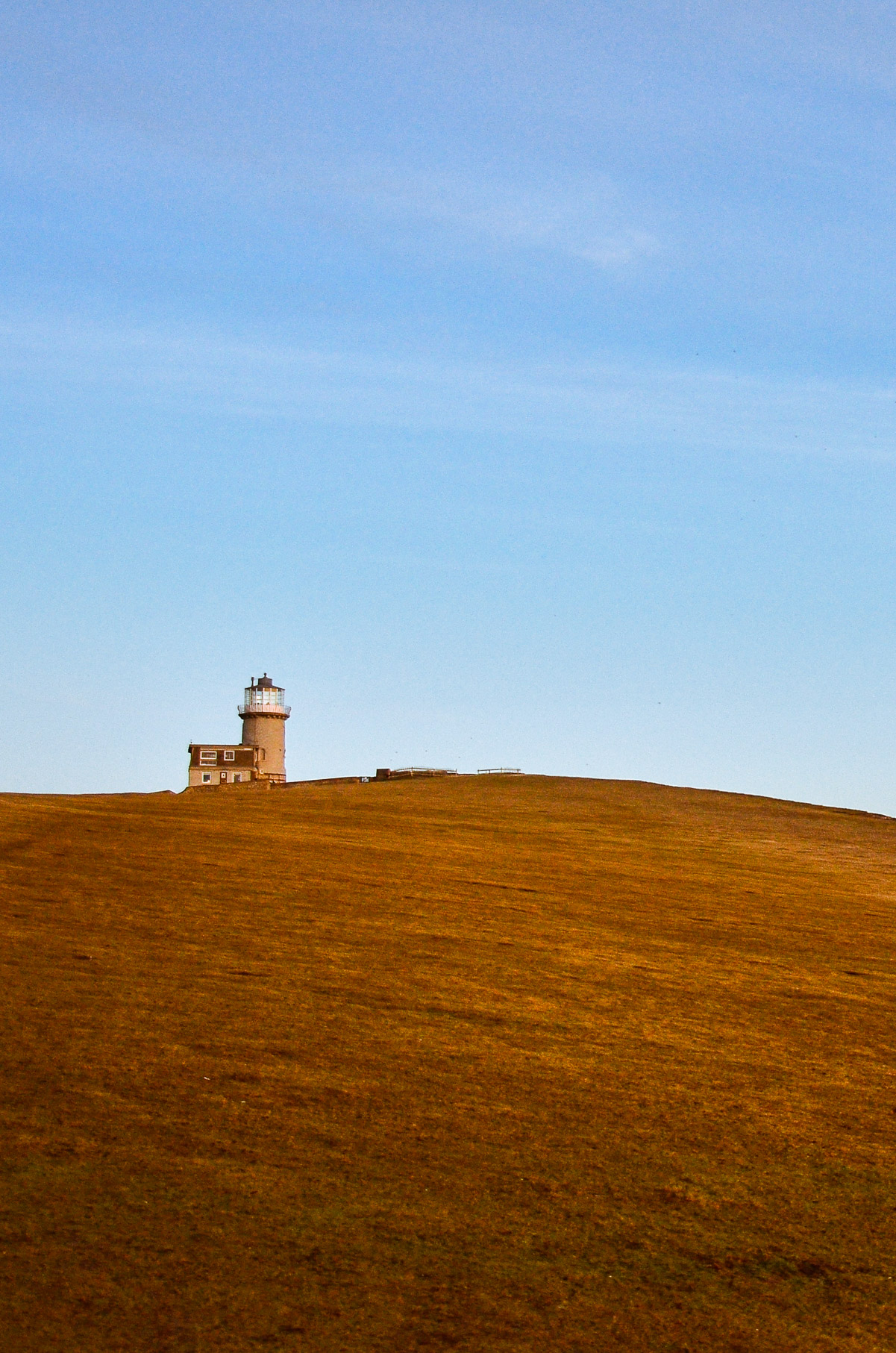 Example of leading lines in travel photography, lighthouse on an orange hill and blue sky