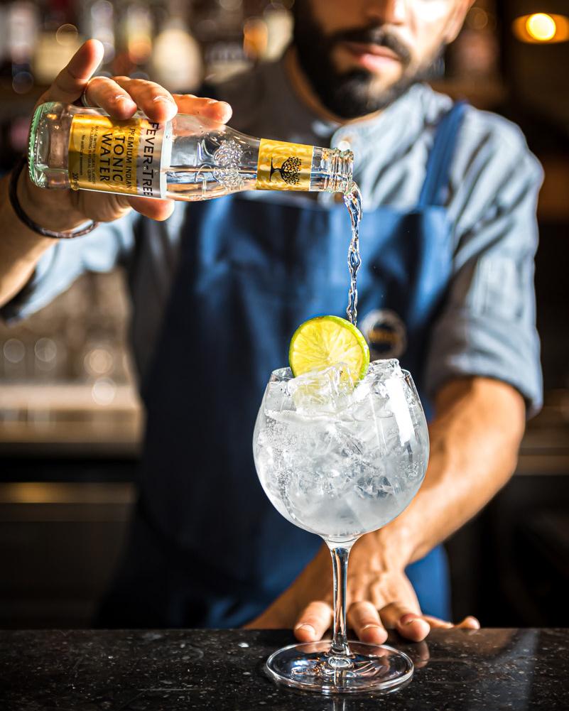 Bartender making gin and tonic shot with a flashgun